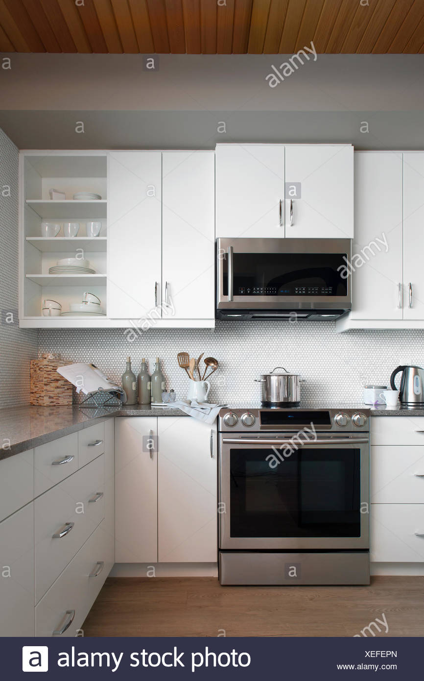 Modern white kitchen with stainless steel appliances - Stock Image