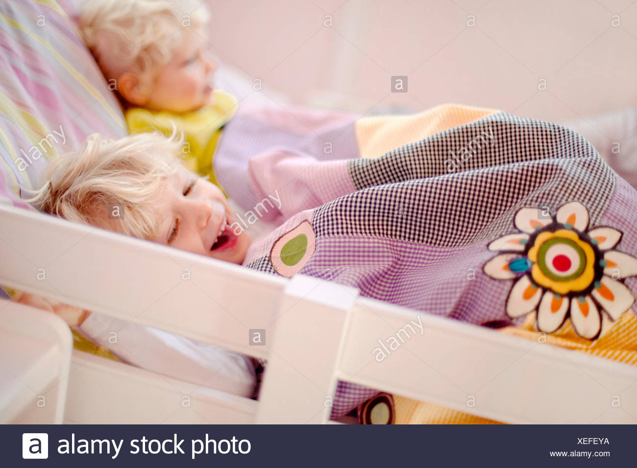 Two young brothers lying in bed, one laughing - Stock Image