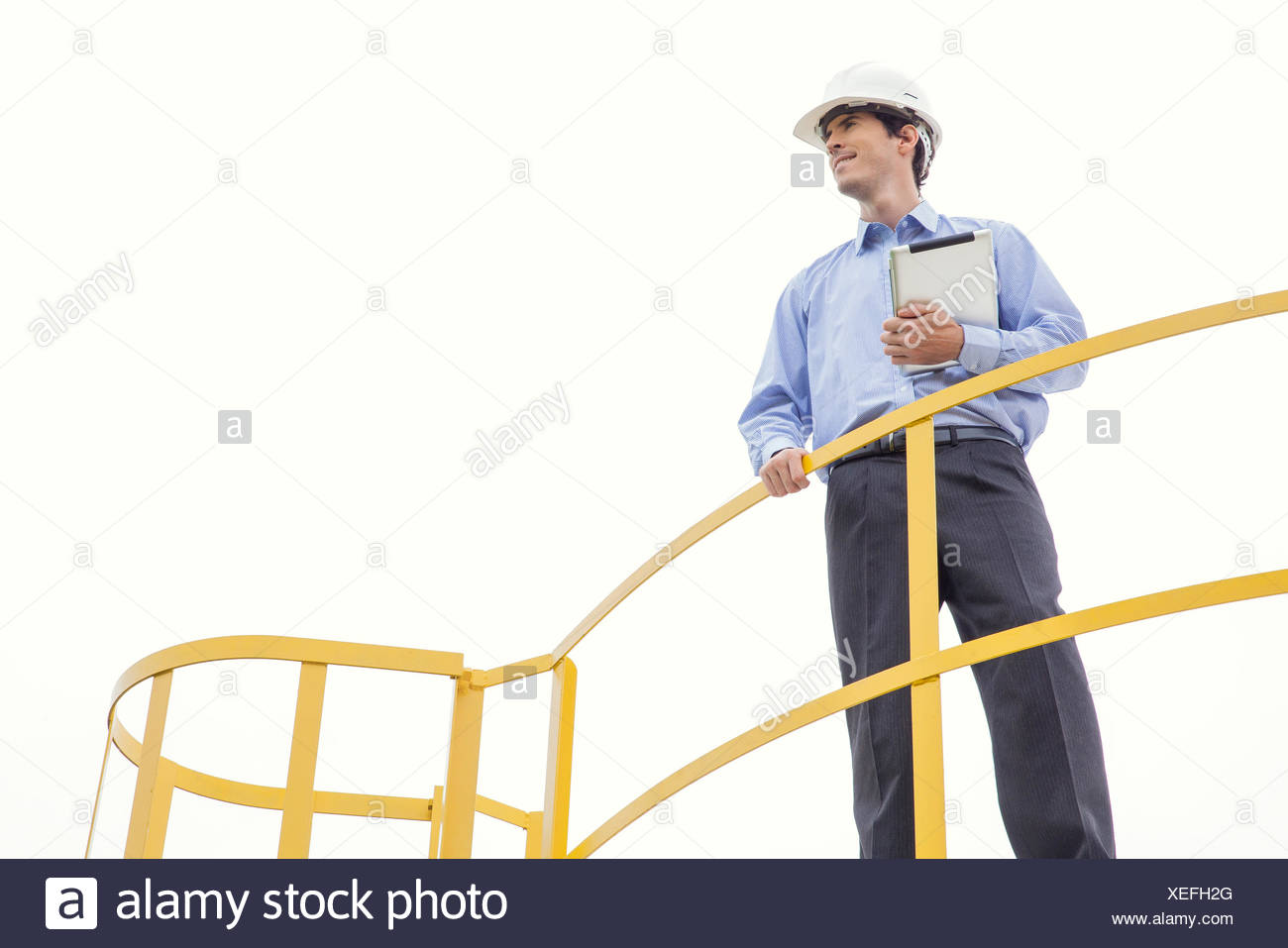Engineer inspecting industrial site, low angle view - Stock Image