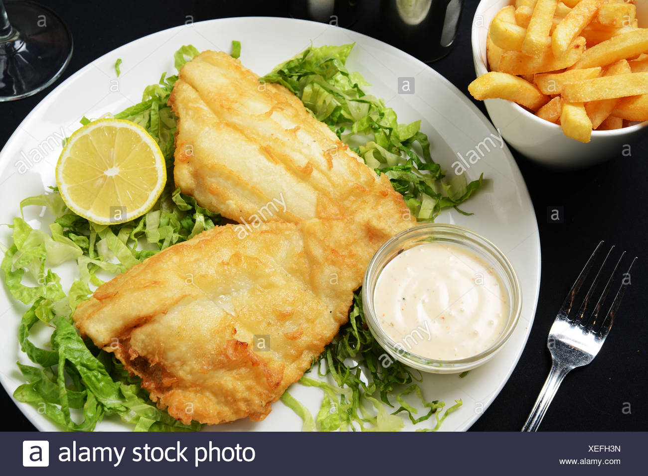 A plate of fried Fish and Chips served on lettuce - Stock Image
