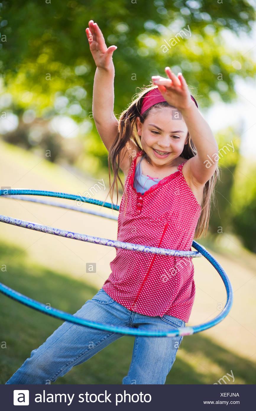 Young girl playing with hula hoop - Stock Image