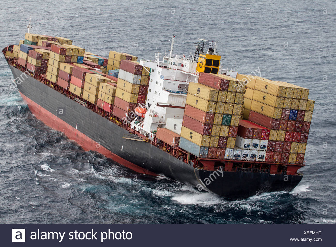 Container ship, MV Rena, approximately 14 hours after becoming grounded on Astrolabe Reef, off of the Port of Tauranga, Bay of P - Stock Image