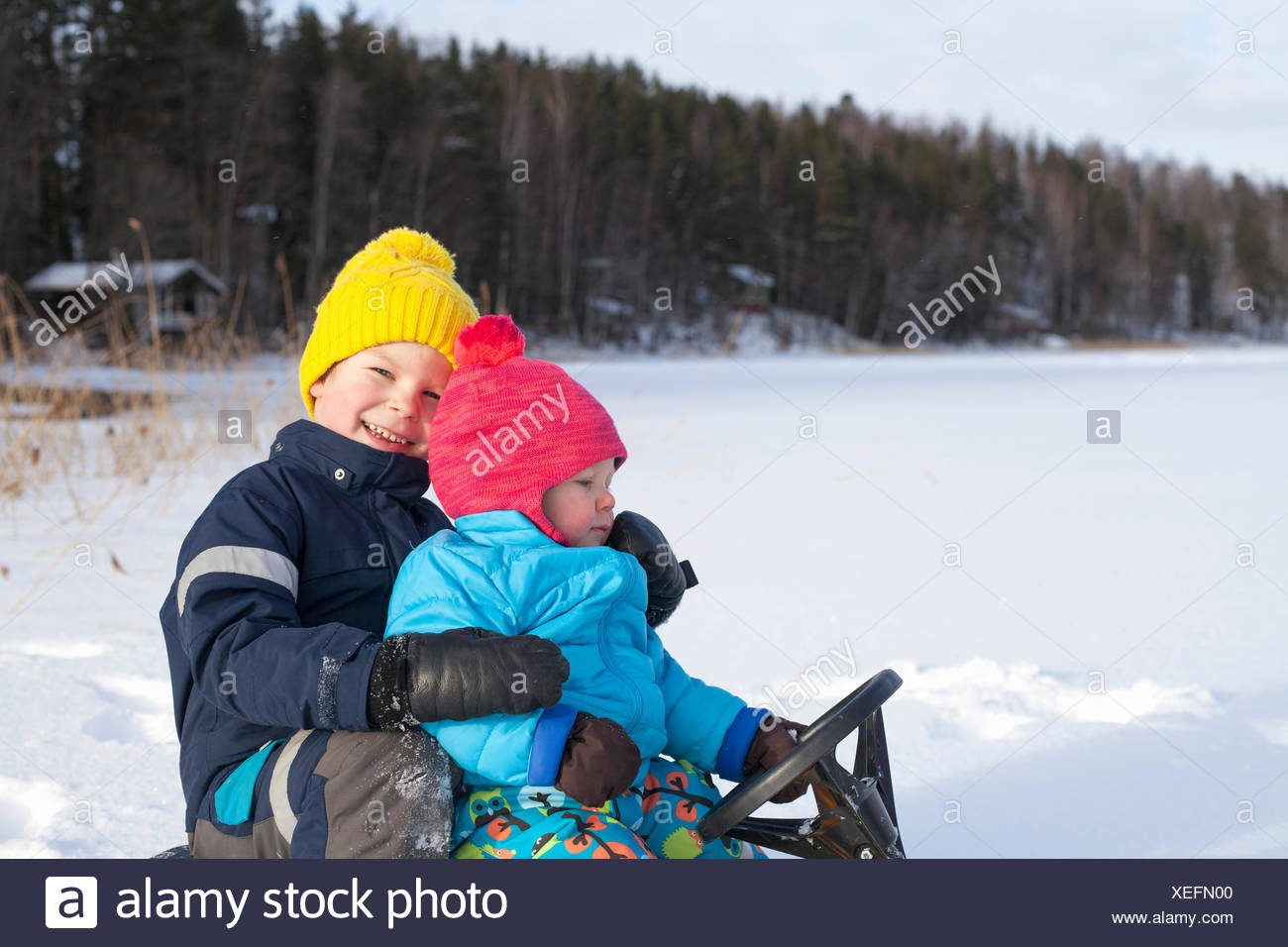 Two young brothers sitting on sledge, in snow covered landscape - Stock Image