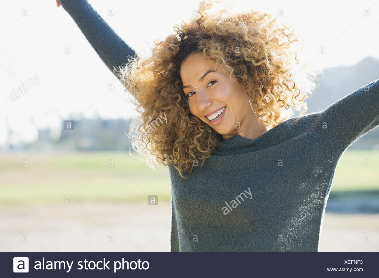 Portrait of woman with arms raised outdoors - Stock Image