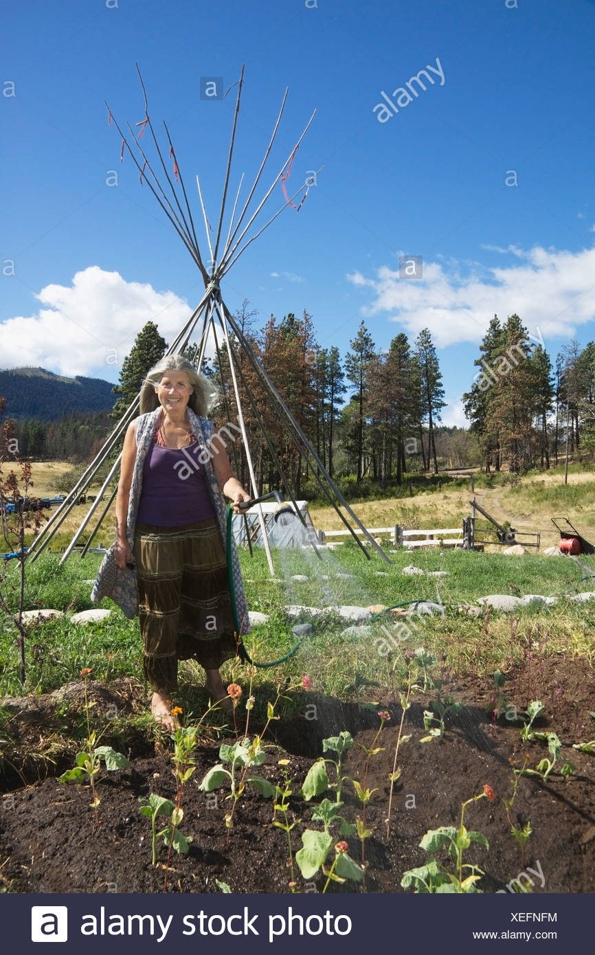 Mojave Kaplan Owner Of The Planting Seeds Project Waters Her Organic Garden; Lytton British Columbia Canada - Stock Image