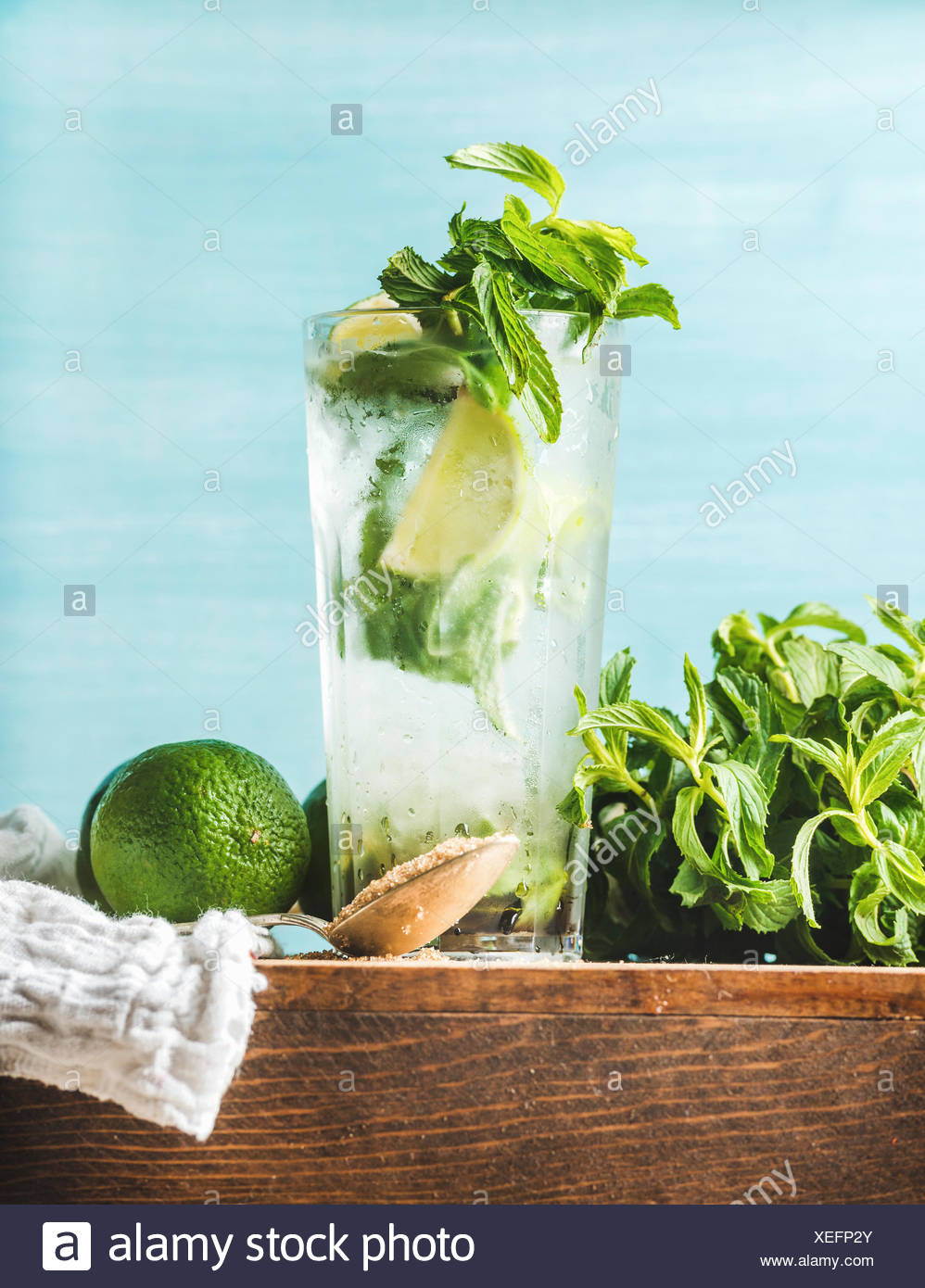 Homemade Mojito cocktail in tall glass served with bunch of mint, brown sugar and limes on wooden board. Turquoise blue backgrou - Stock Image