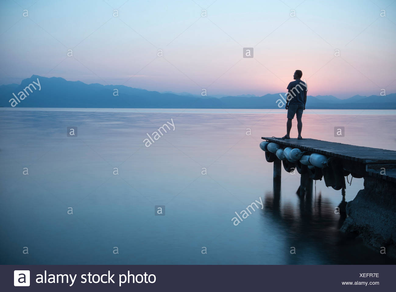 Man standing at a jetty and looking at the lake - Stock Image