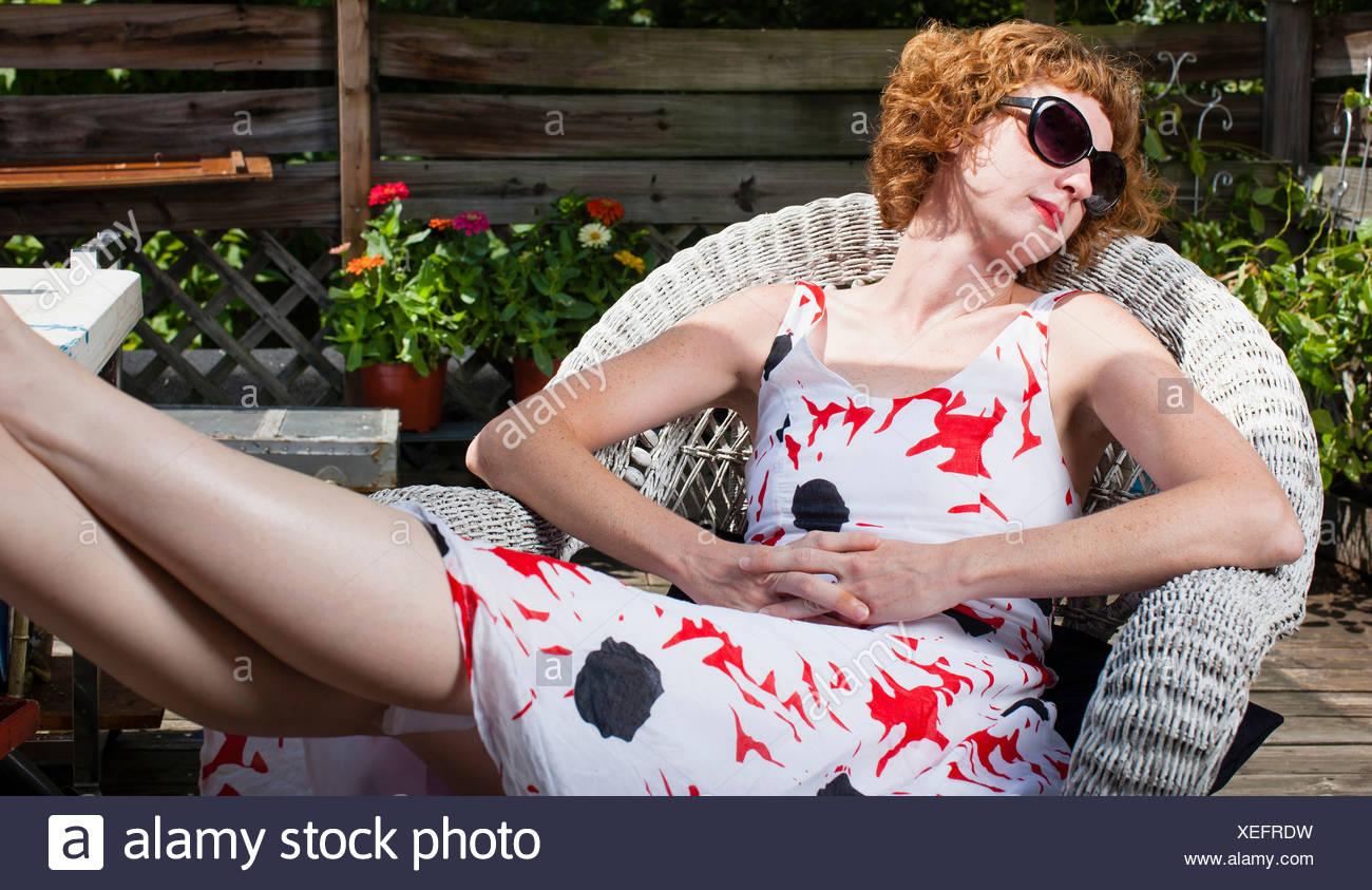 Woman sunbathing in patio chair - Stock Image