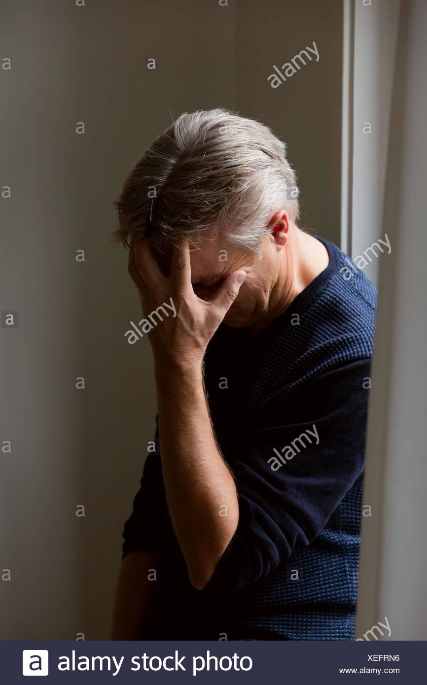 Man with headache or hiding face or very upset or migraine attack - Stock Image