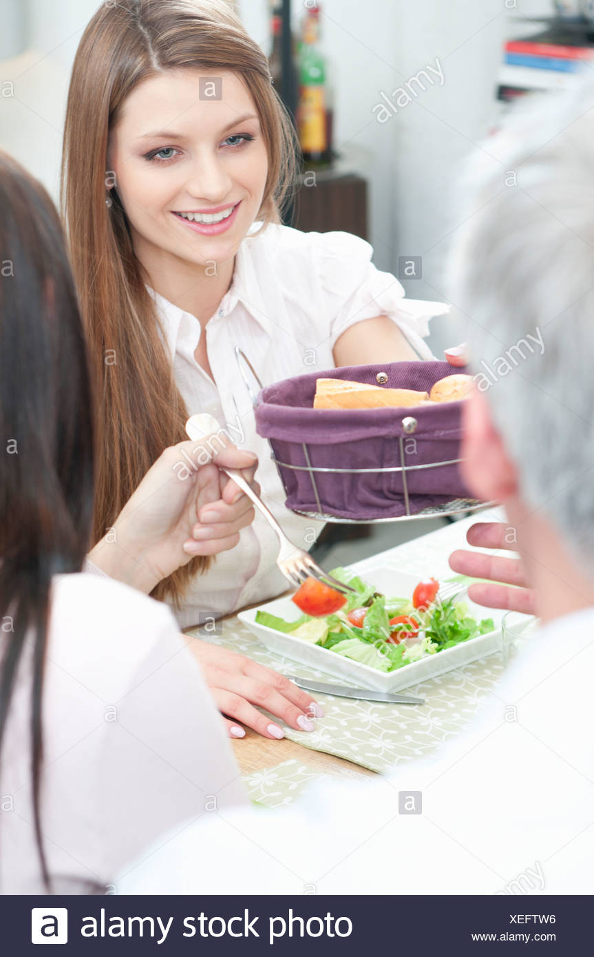 Passing the bread at lunch - Stock Image