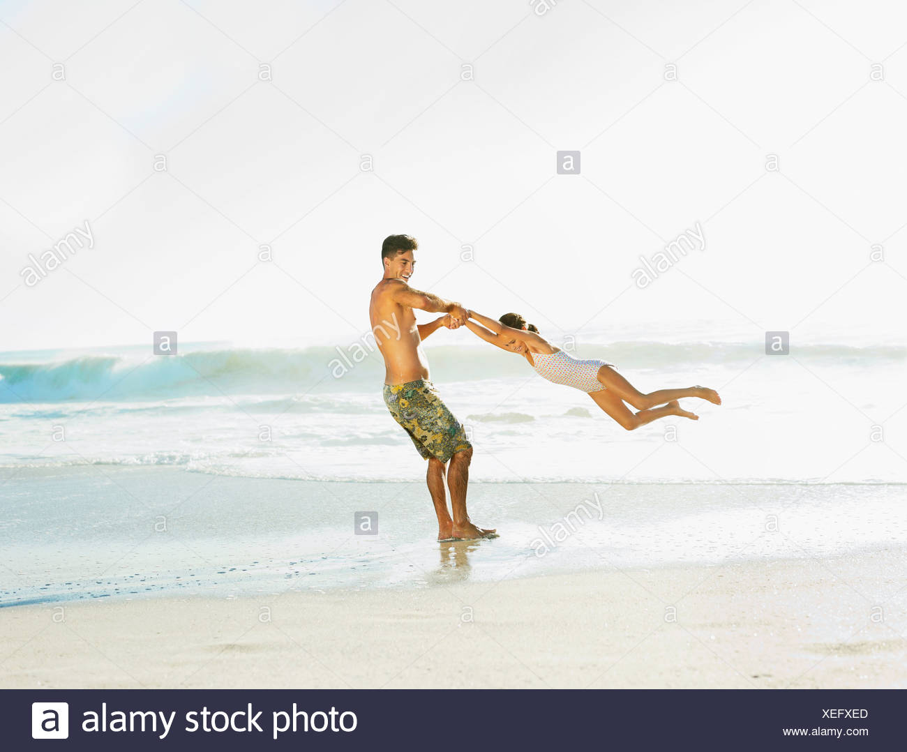 Father swinging daughter on beach - Stock Image