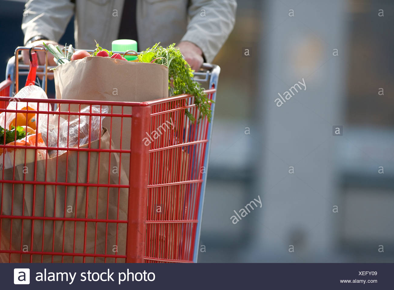 Man pushing grocery cart full of groceries - Stock Image