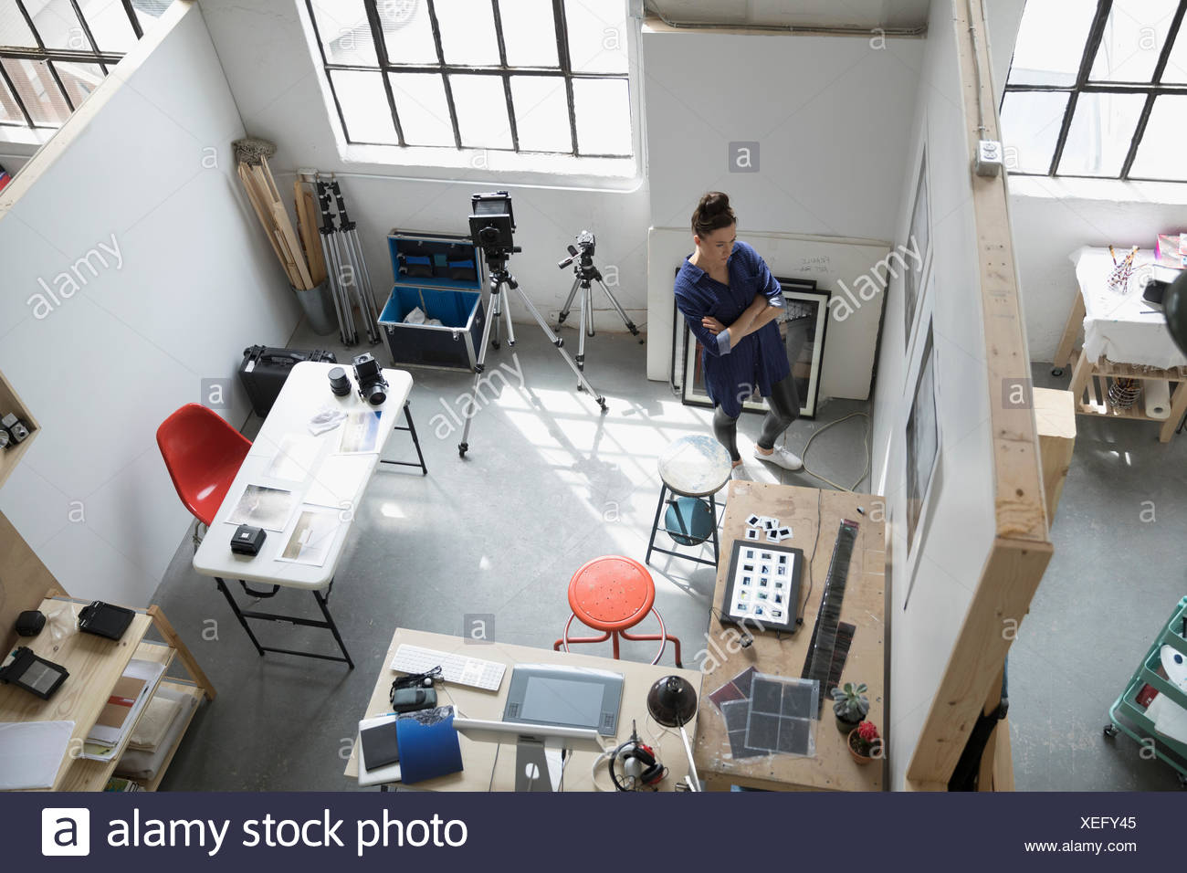 Female photographer viewing photograph prints on wall in art studio - Stock Image