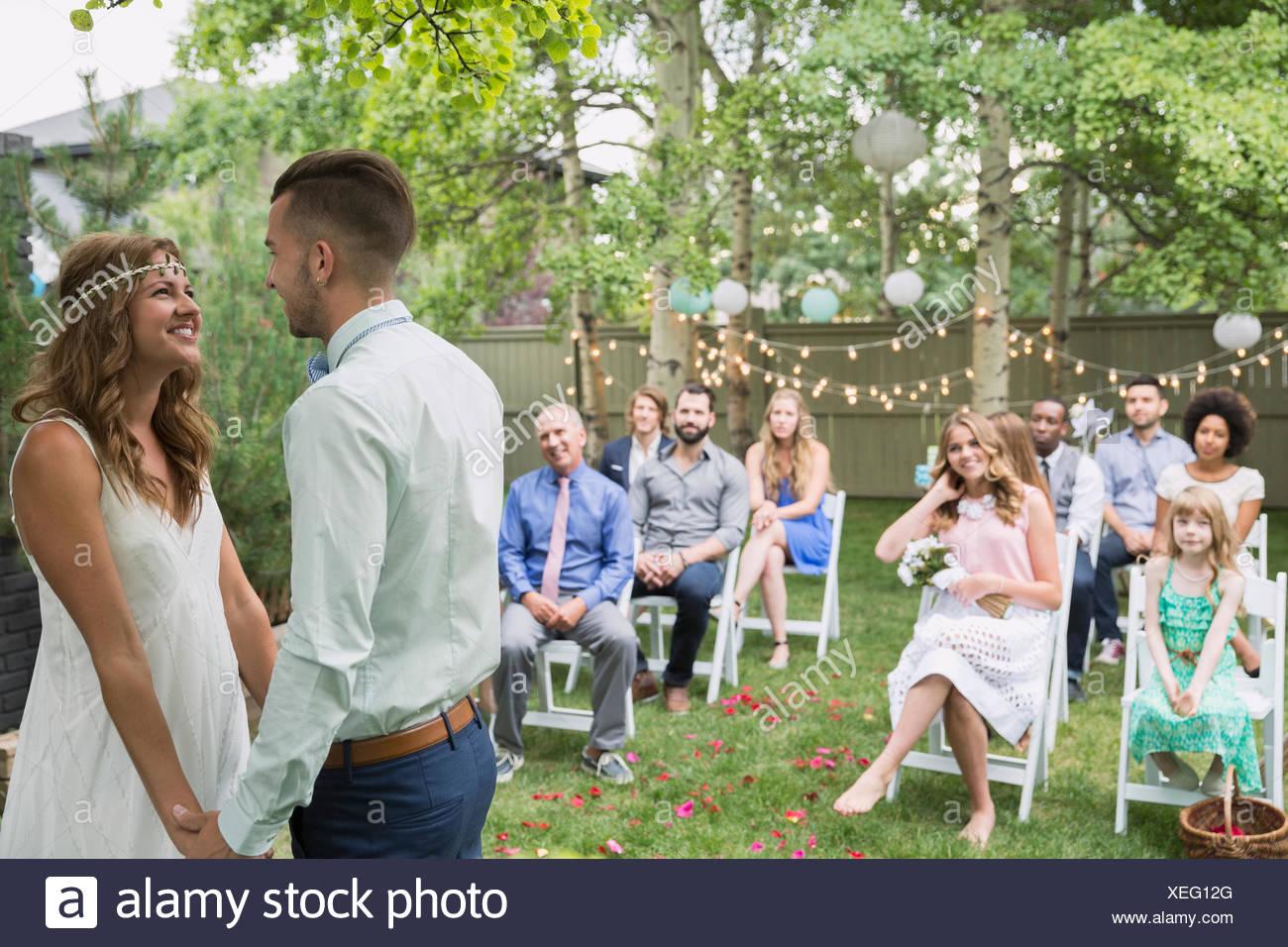 Wedding guests watching bride and groom backyard wedding - Stock Image