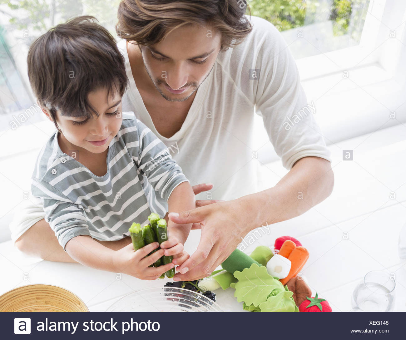 Happy young family preparing vegetables at home - Stock Image