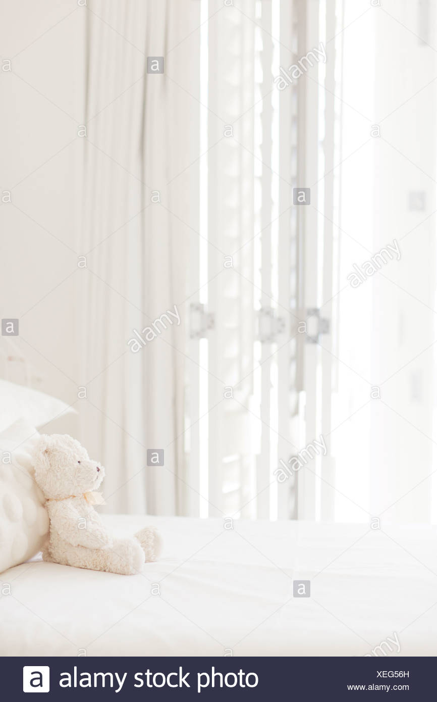 Teddy bear on white bed - Stock Image