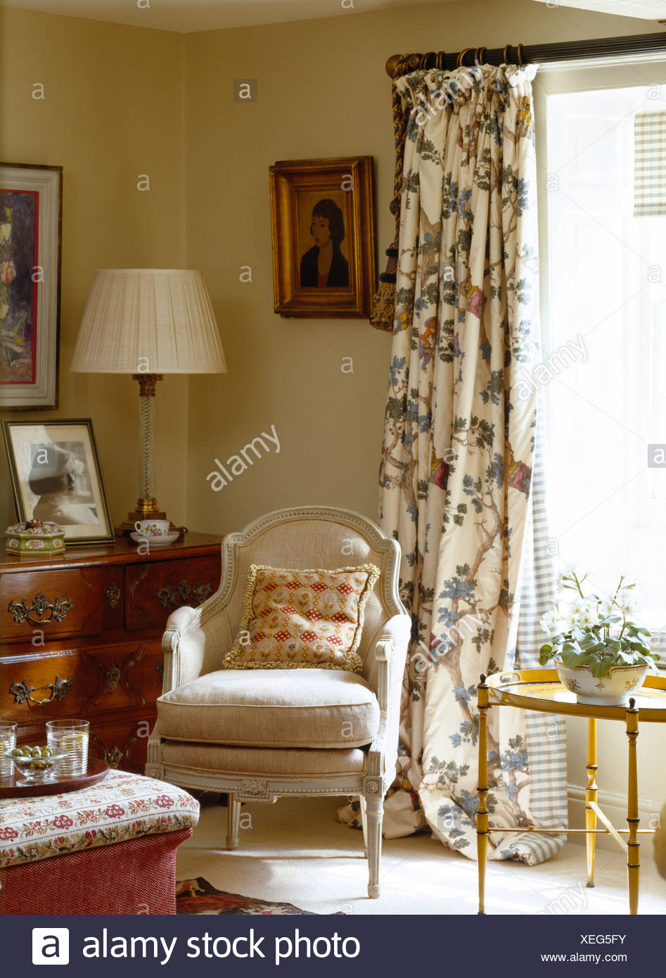 Upholstered French Style Armchair In Front Of Window With Floral