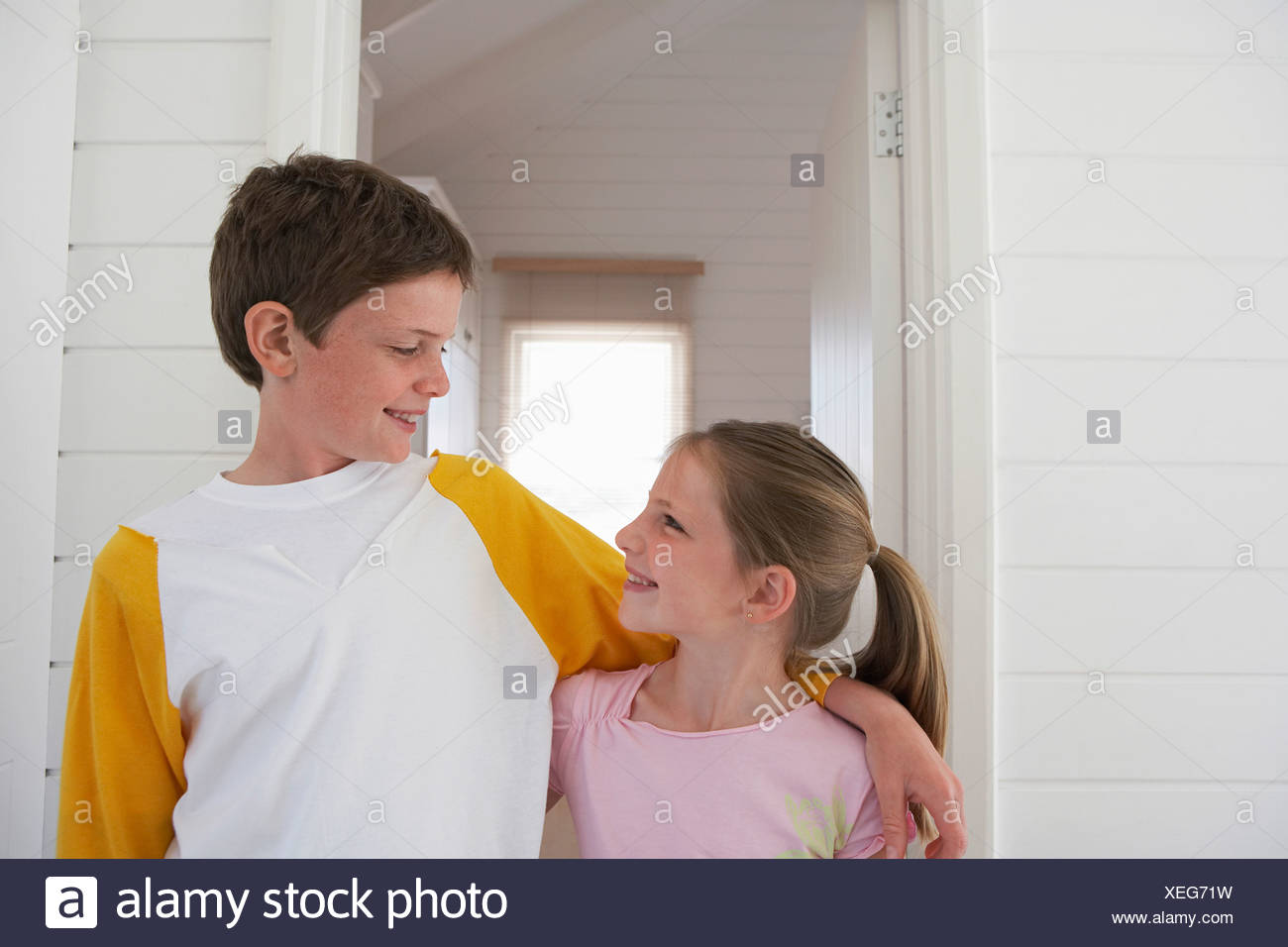 Young boy with arm around girl standing in house, half length - Stock Image