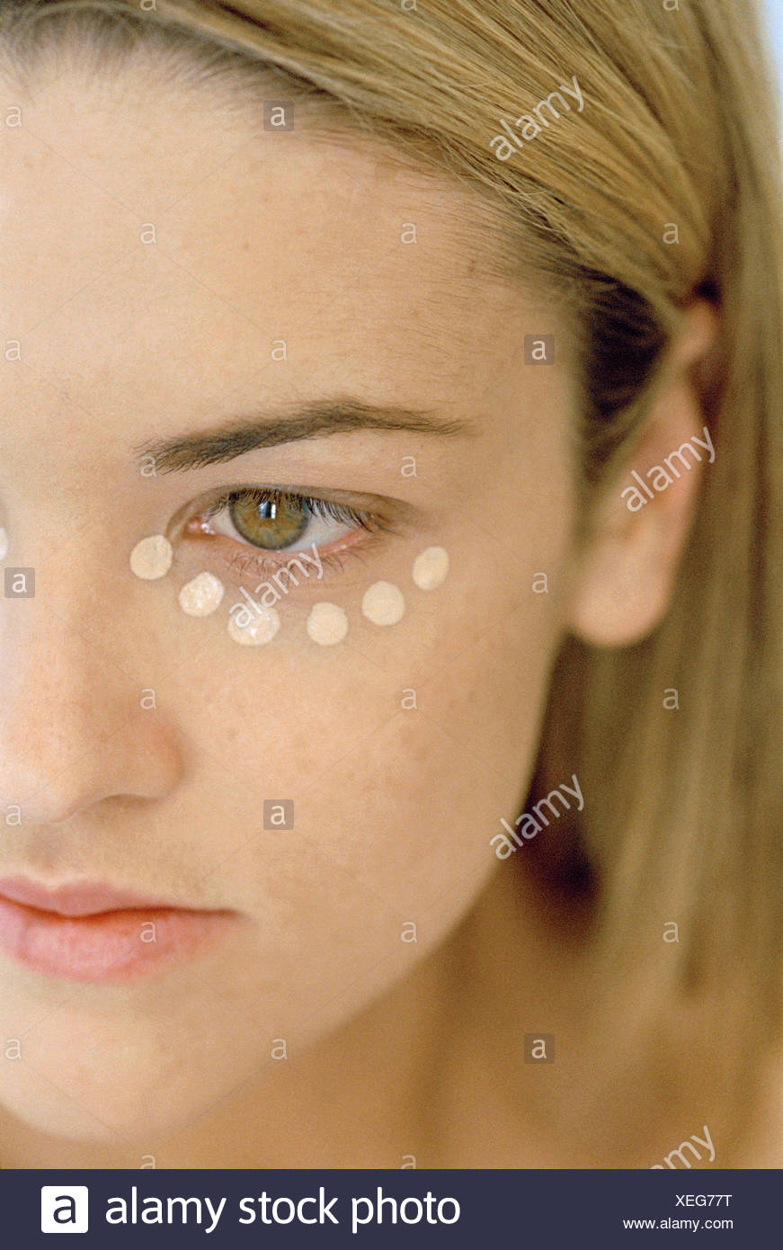 Close up of half face of female straight shoulder length blonde hair tucked behind ear spots of concealer under eye looking - Stock Image