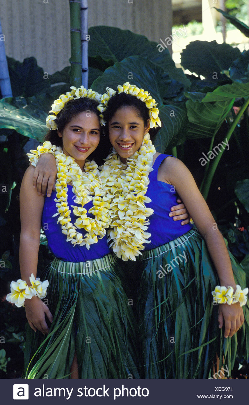 Young girls (wahines) with Ti leaf skirts and plumeria leis - Stock Image