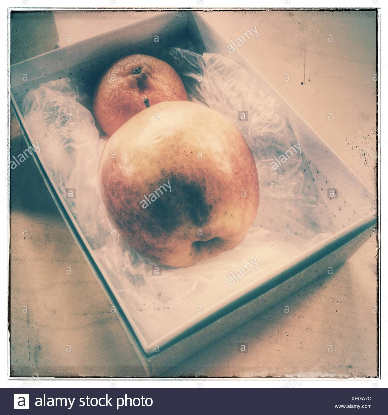 Closer-Up Of Apple And Orange In Box - Stock Image