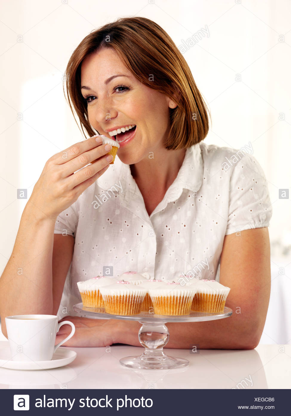 WOMAN EATING A CUPCAKE - Stock Image