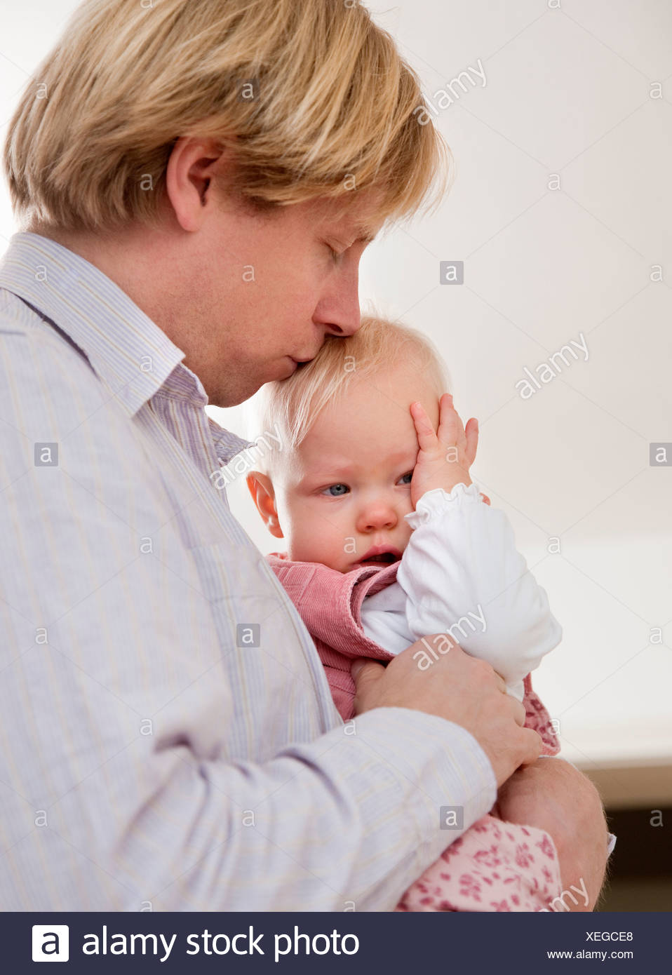 father comforting crying baby - Stock Image