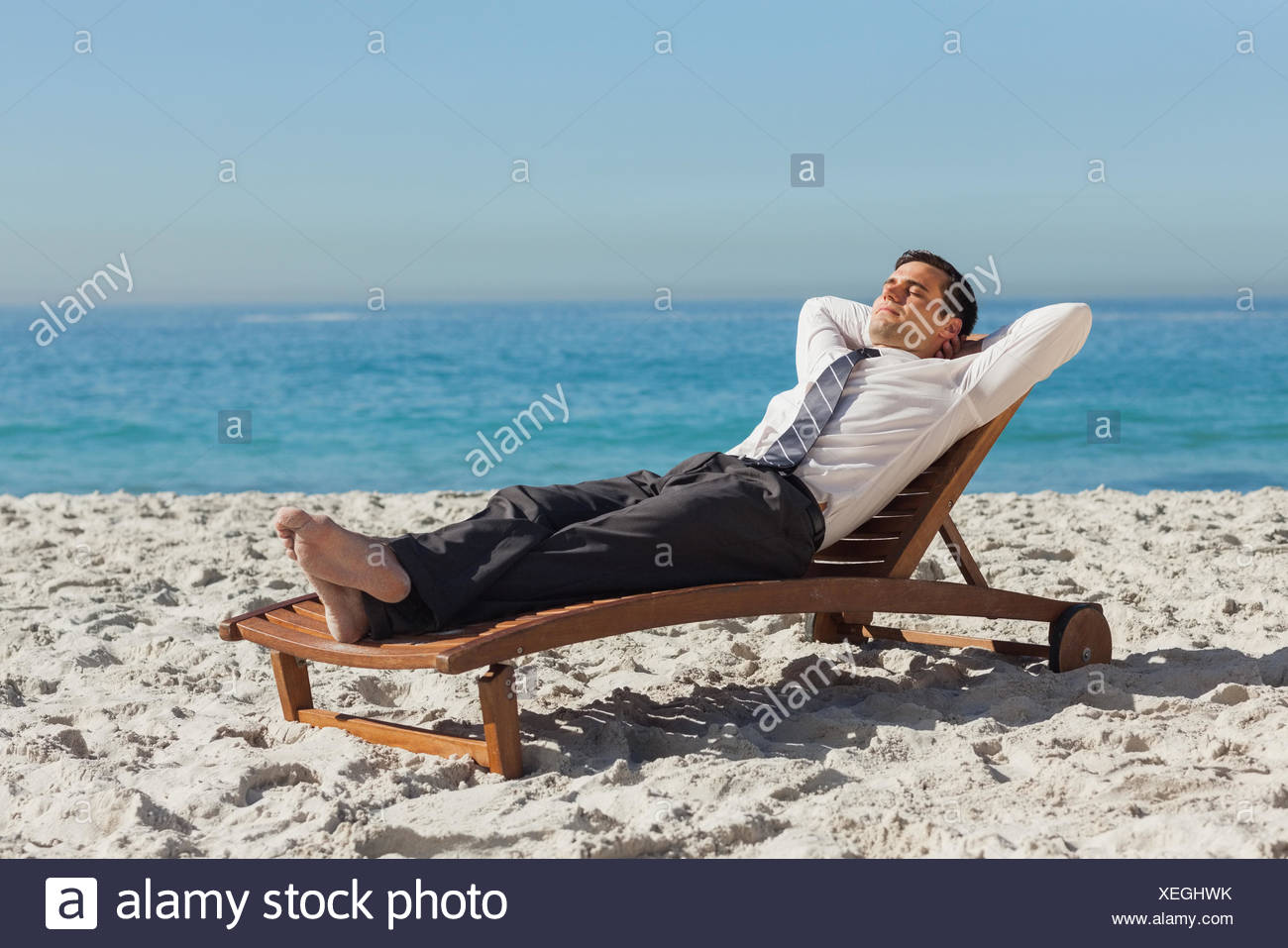 275028a5b8 Young businessman relaxing on a deck chair on the beach Stock Photo ...