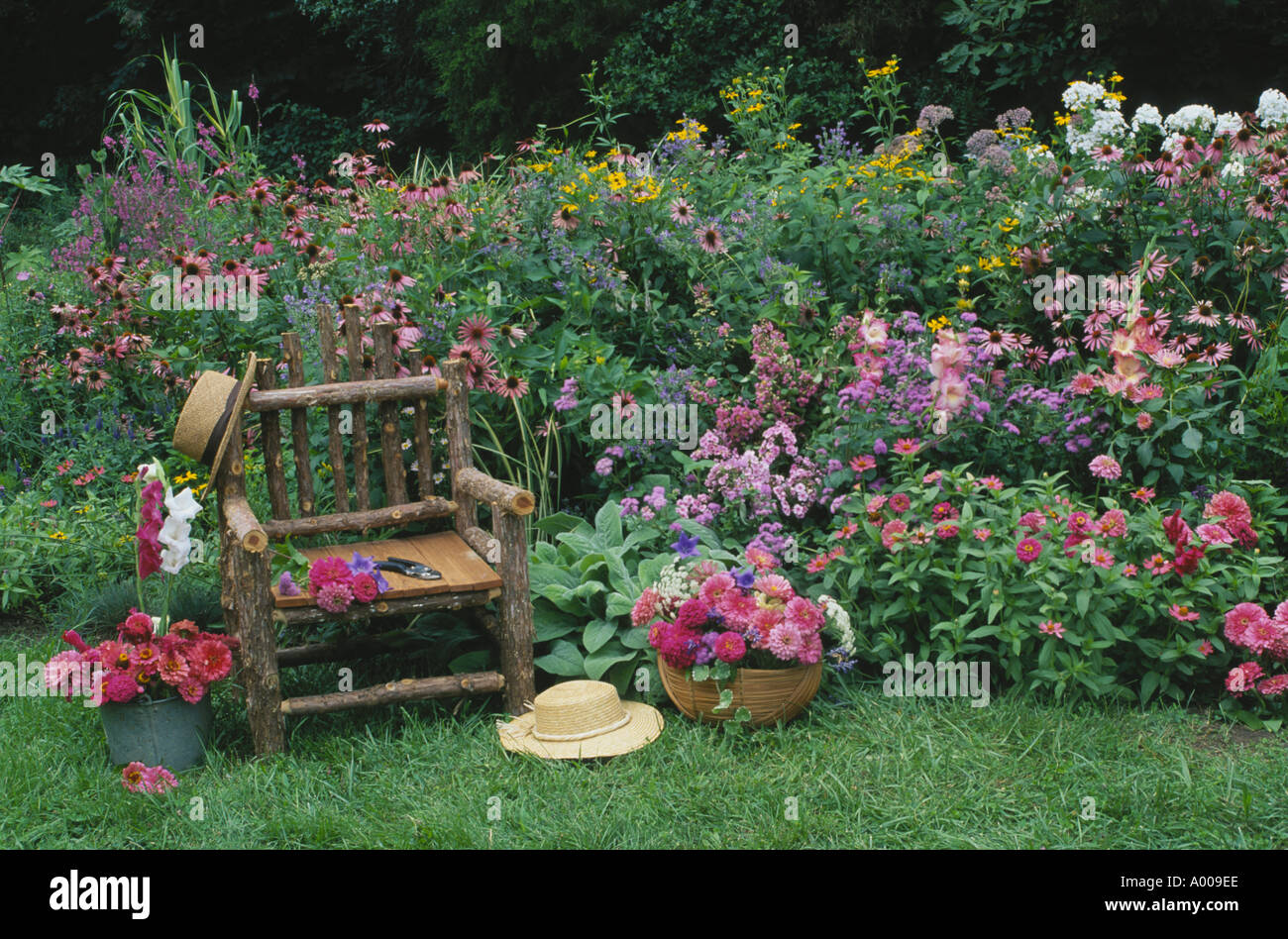 Romantic garden rustic chair in home flower garden of pinks and reds stock photo royalty free - Rustic flower gardens ...