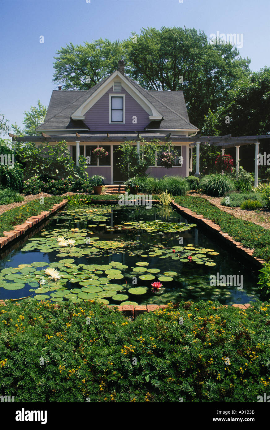 pastel painted wood cottage with large decorative fish pond in