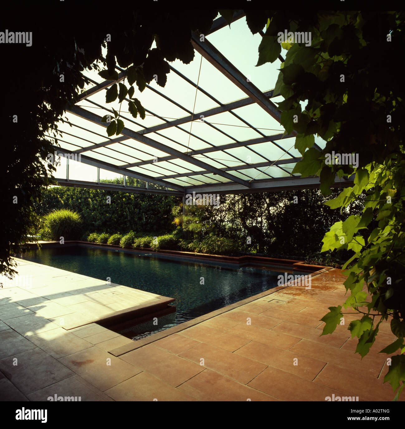 Retractable Glass Roof Above Indoor Swimming Pool With Terracotta Tiled  Surround