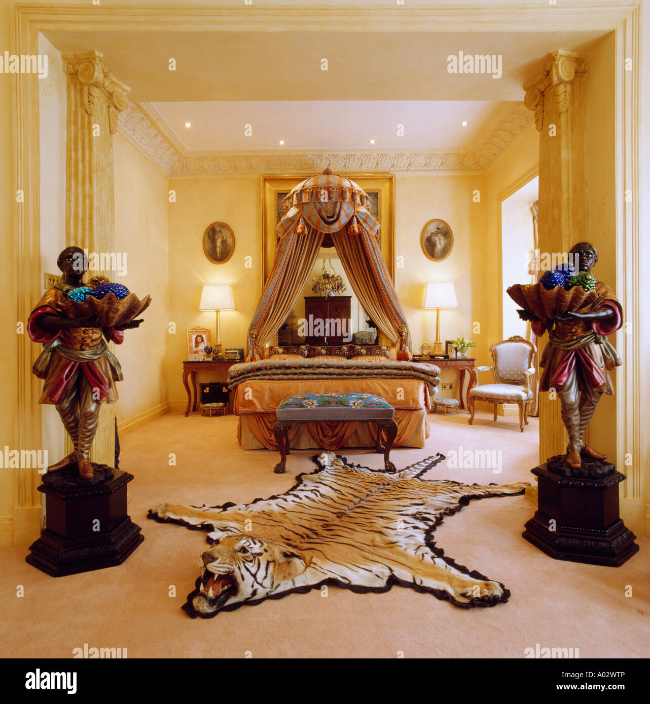 Townhouse Bedroom With Large Statues On Plinths And Tigerskin Rug On Floor    Stock Image