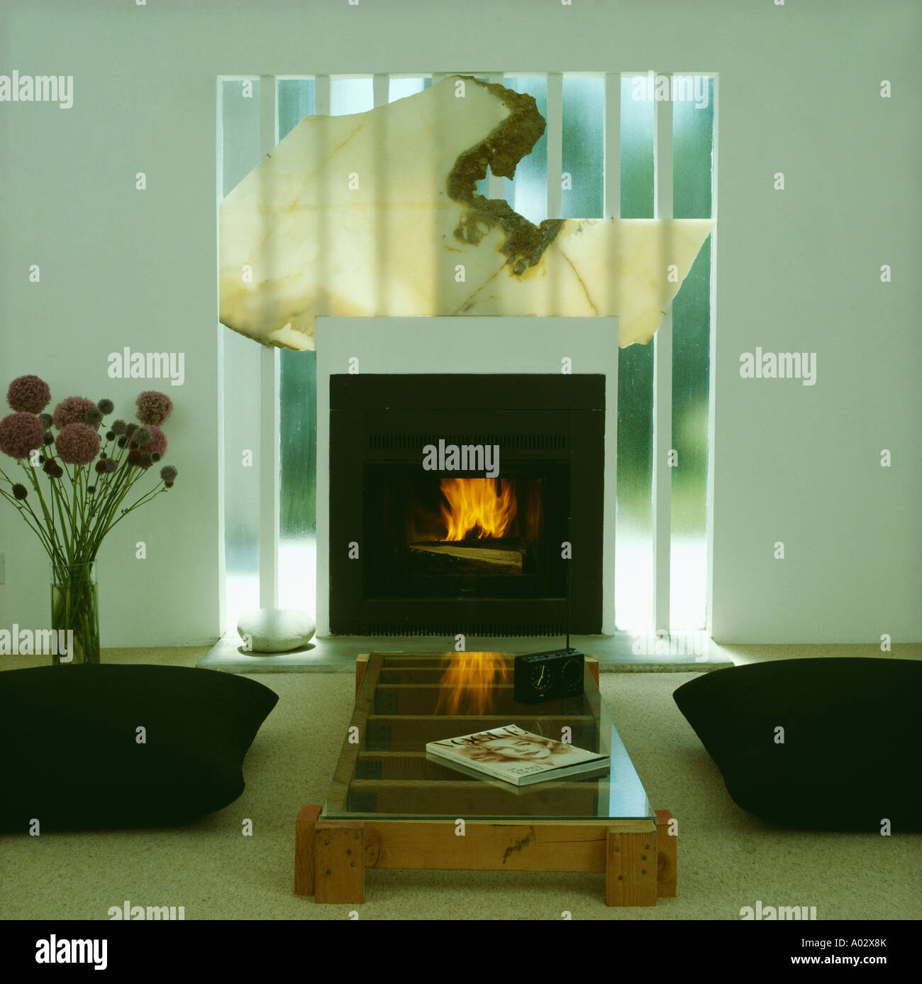 Modern mirrored fireplace in livingroom with black chairs and