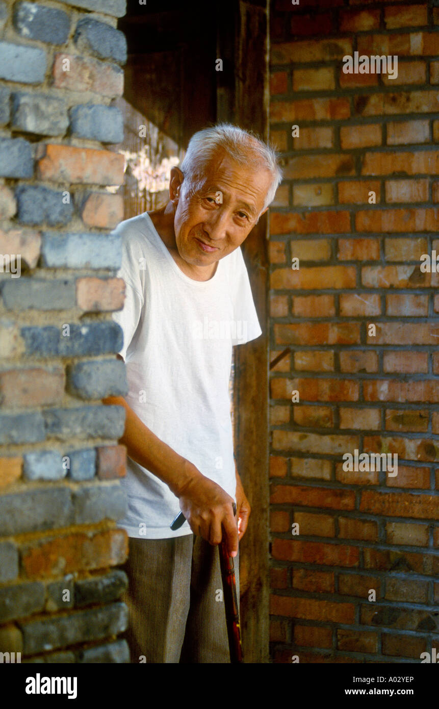 Old Chinese Man With Walking Stick At The Front Door Of