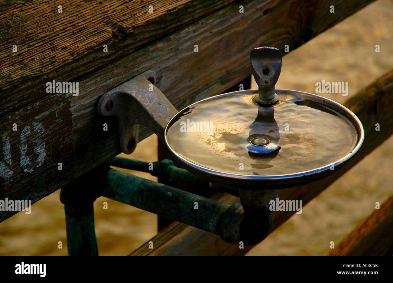rough drinking water fountain mounted on wood railing in afternoon sunlight at an outdoor beach area