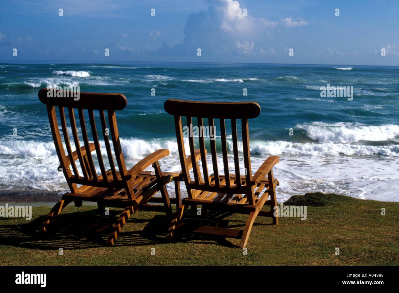 pair of teak beach chairs on tropical beach Stock Photo Royalty
