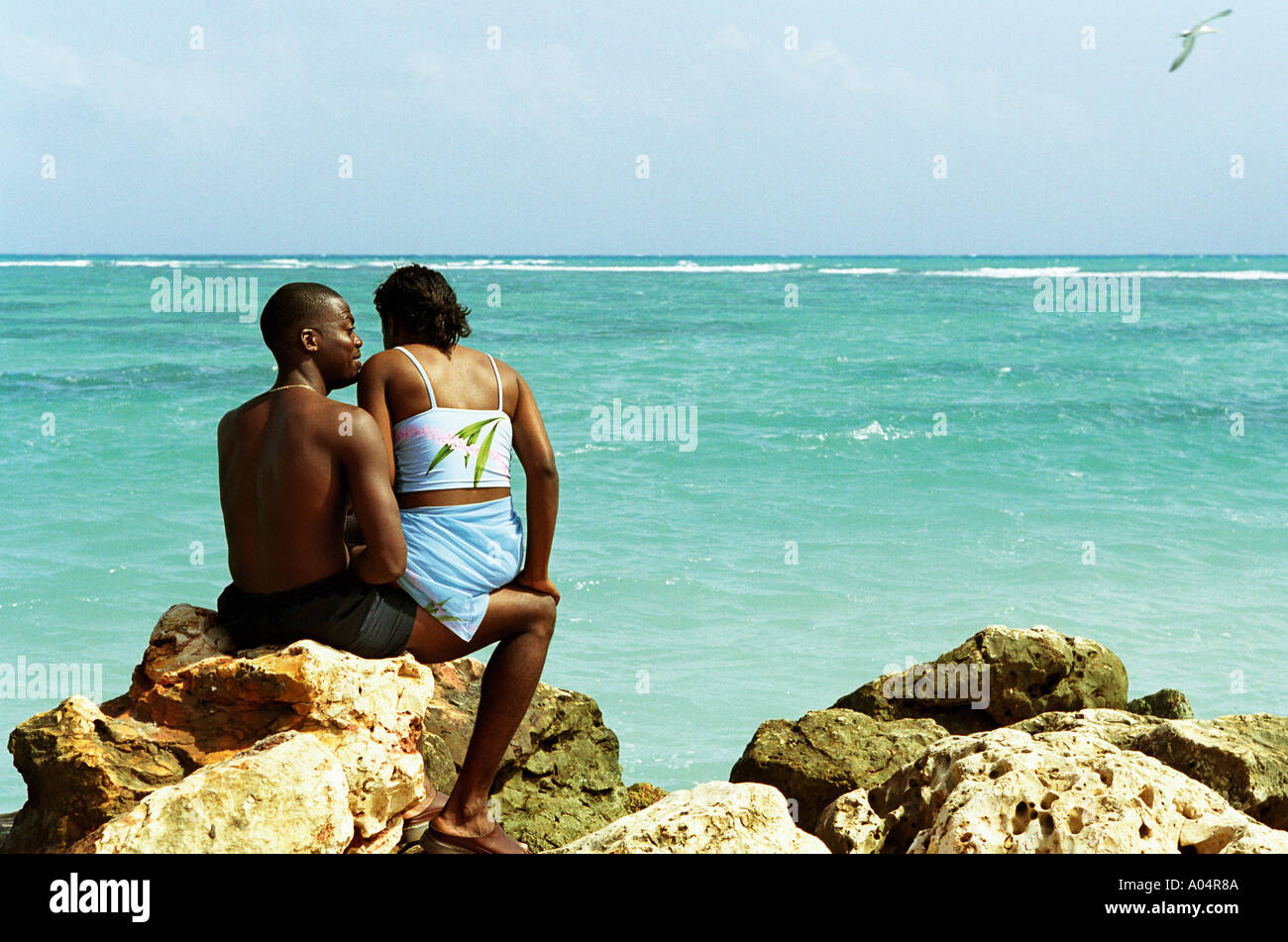 Couple Sitting By The Sea At Hellshire Beach Jamaica