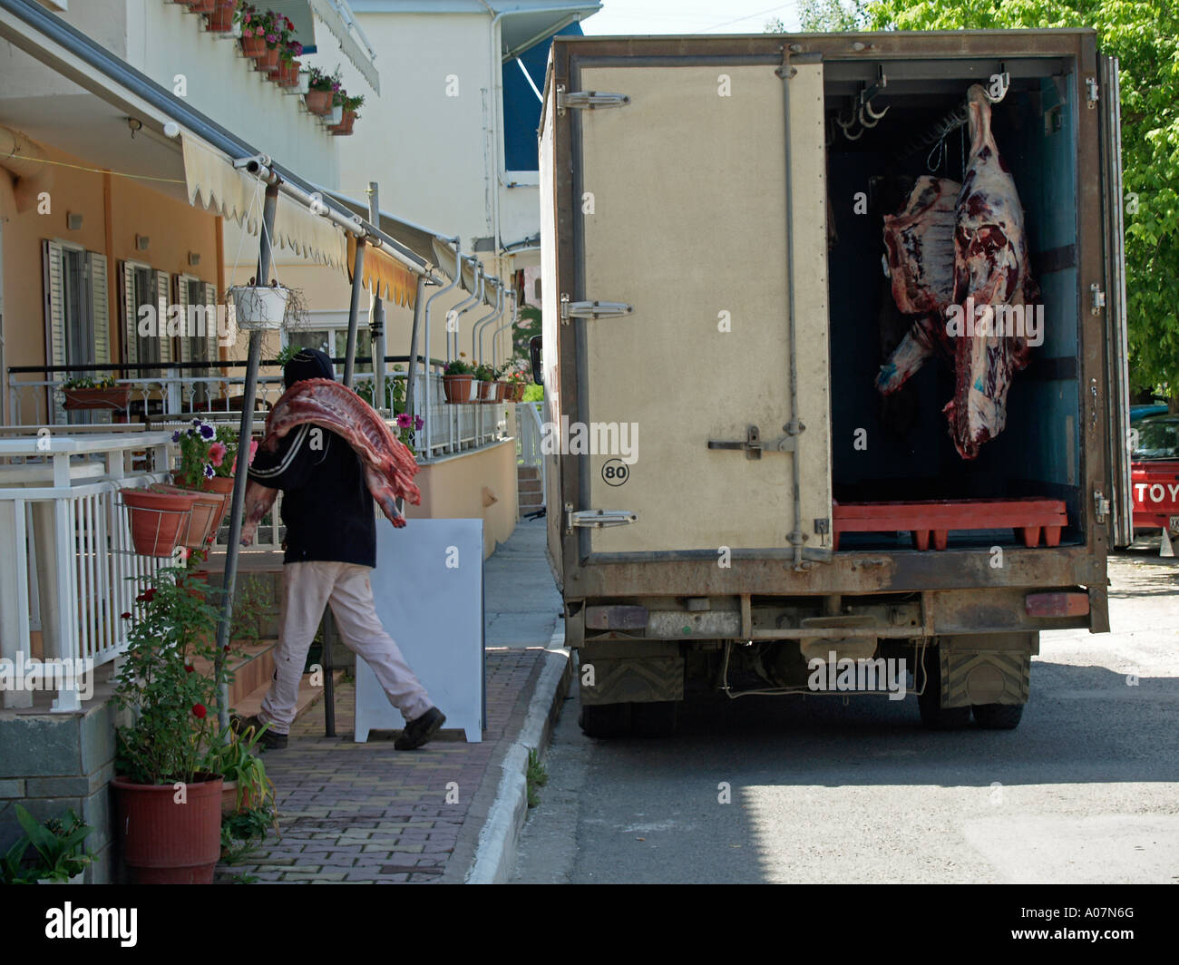 Delivery Of Meat With A Lorry To Butchers Shop In Greece Man Carrying Half Bull The