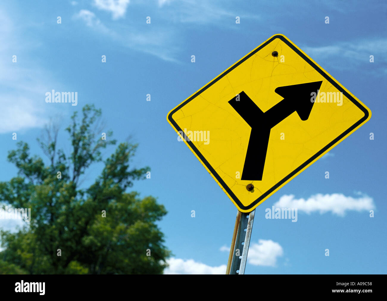 Yellow diamond-shaped road branches off ahead road sign ...