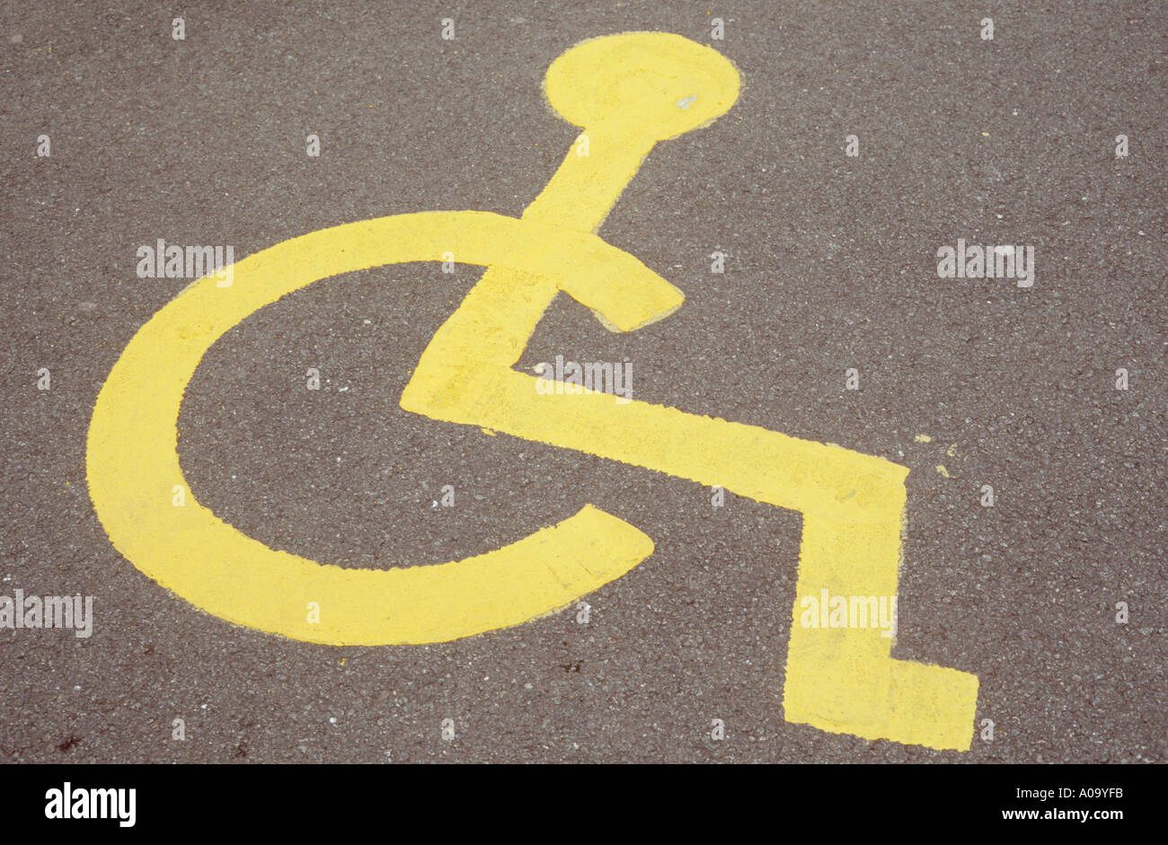 Symbol of person in wheelchair painted in yellow on road or symbol of person in wheelchair painted in yellow on road or carpark surface indicating parking bay for disabled people only buycottarizona