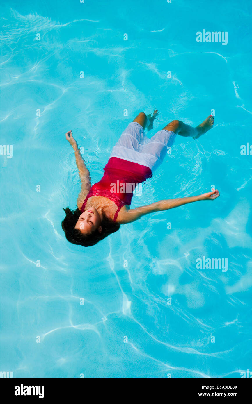 teen girl floating on her back in a swimming pool with her clothes stock photo royalty free