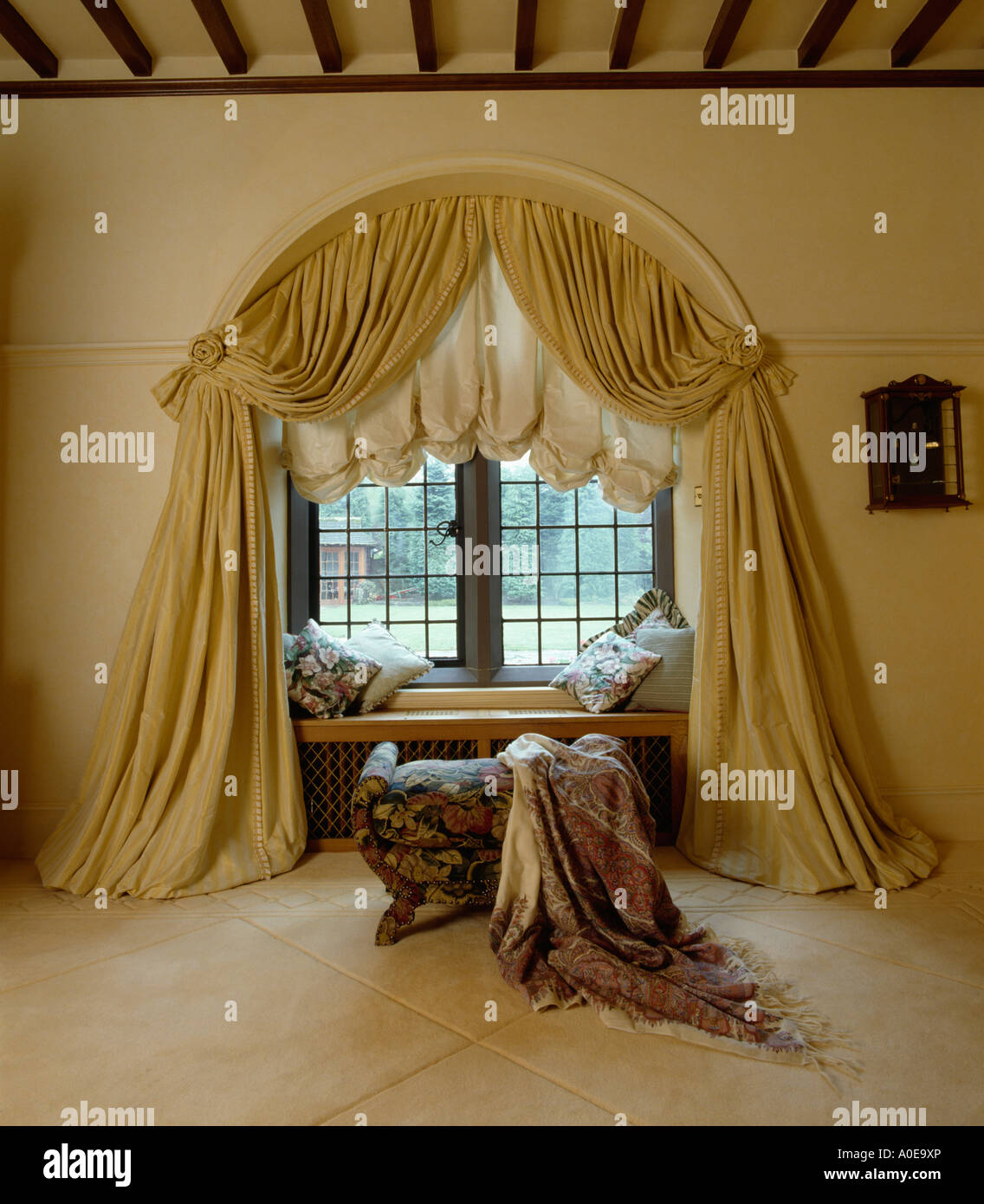 Cream Draped Curtains And Festoon Blind On Arched Window In Bedroom With  Patterned Throw Onstool In Front Of Window
