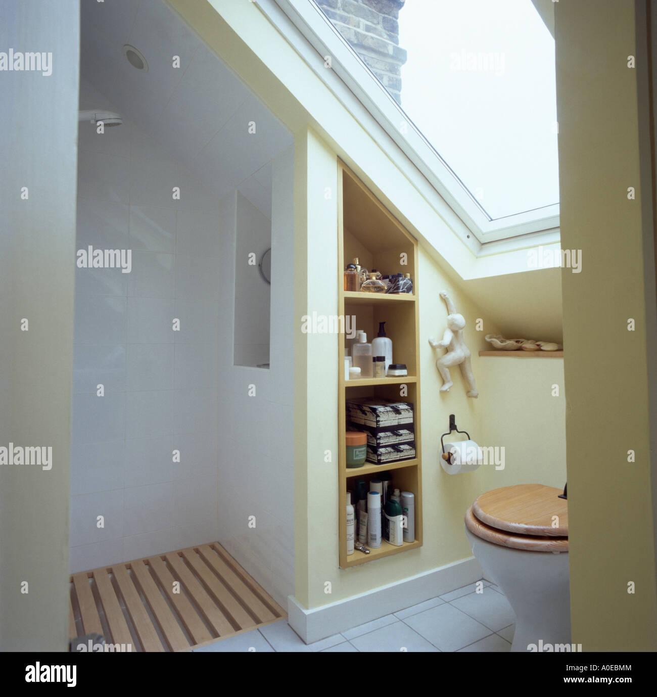 Shower And Shelves In Modern White Attic Bathroom With Wooden Bathmat