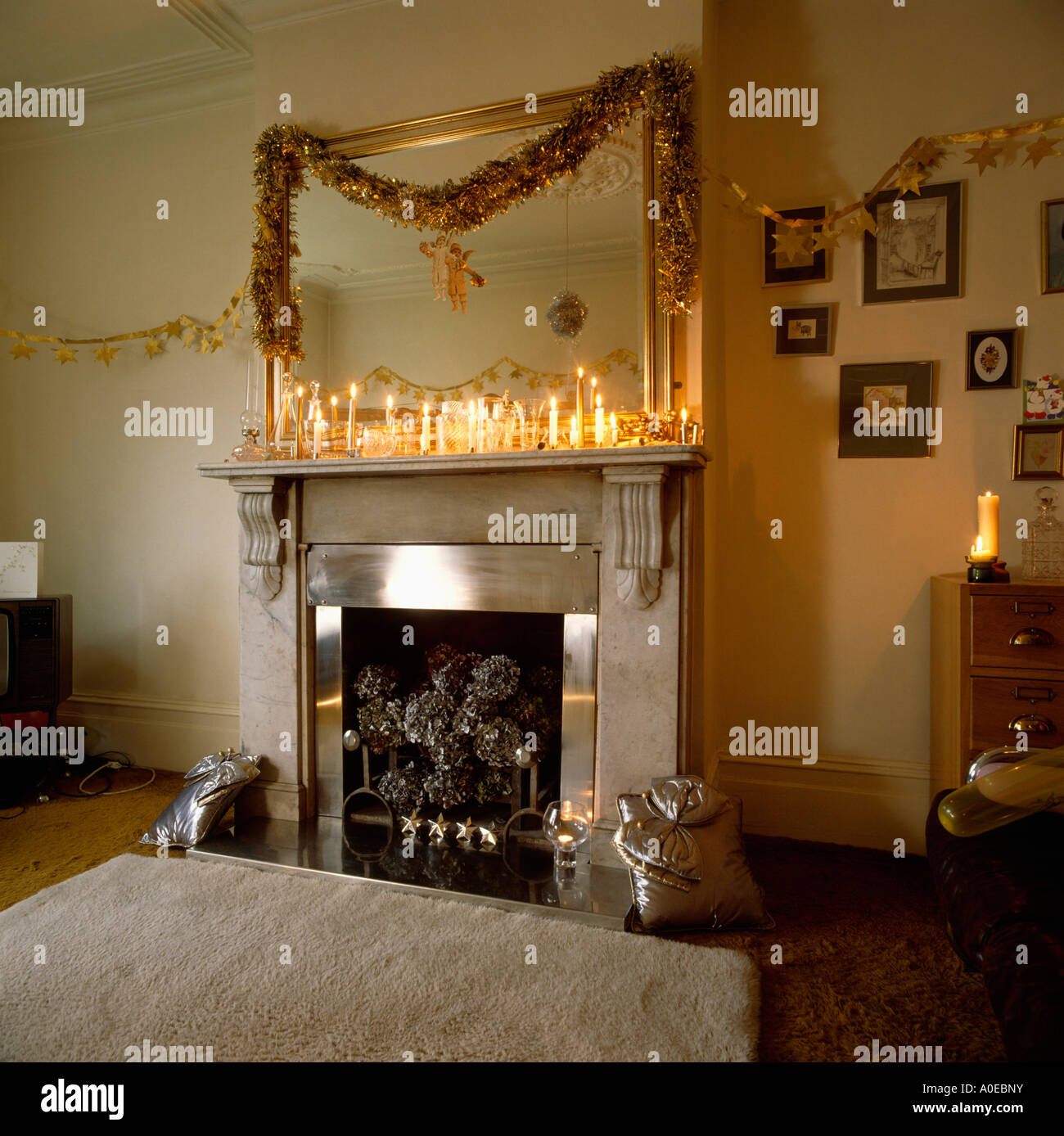 Mirror above marble fireplace with lighted candles and garland ...