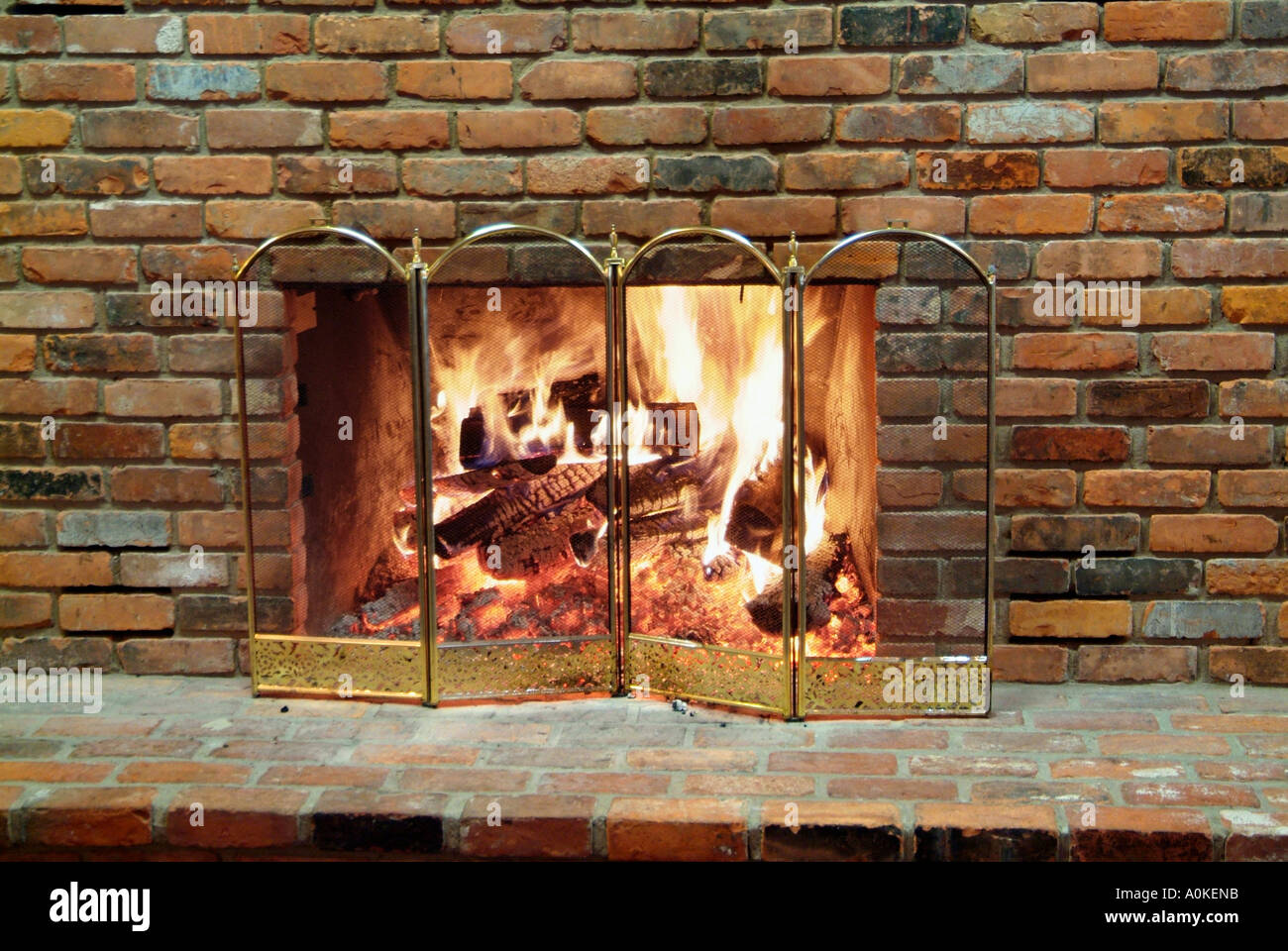 brick enclosed fireplace with a natural log fire stock photo