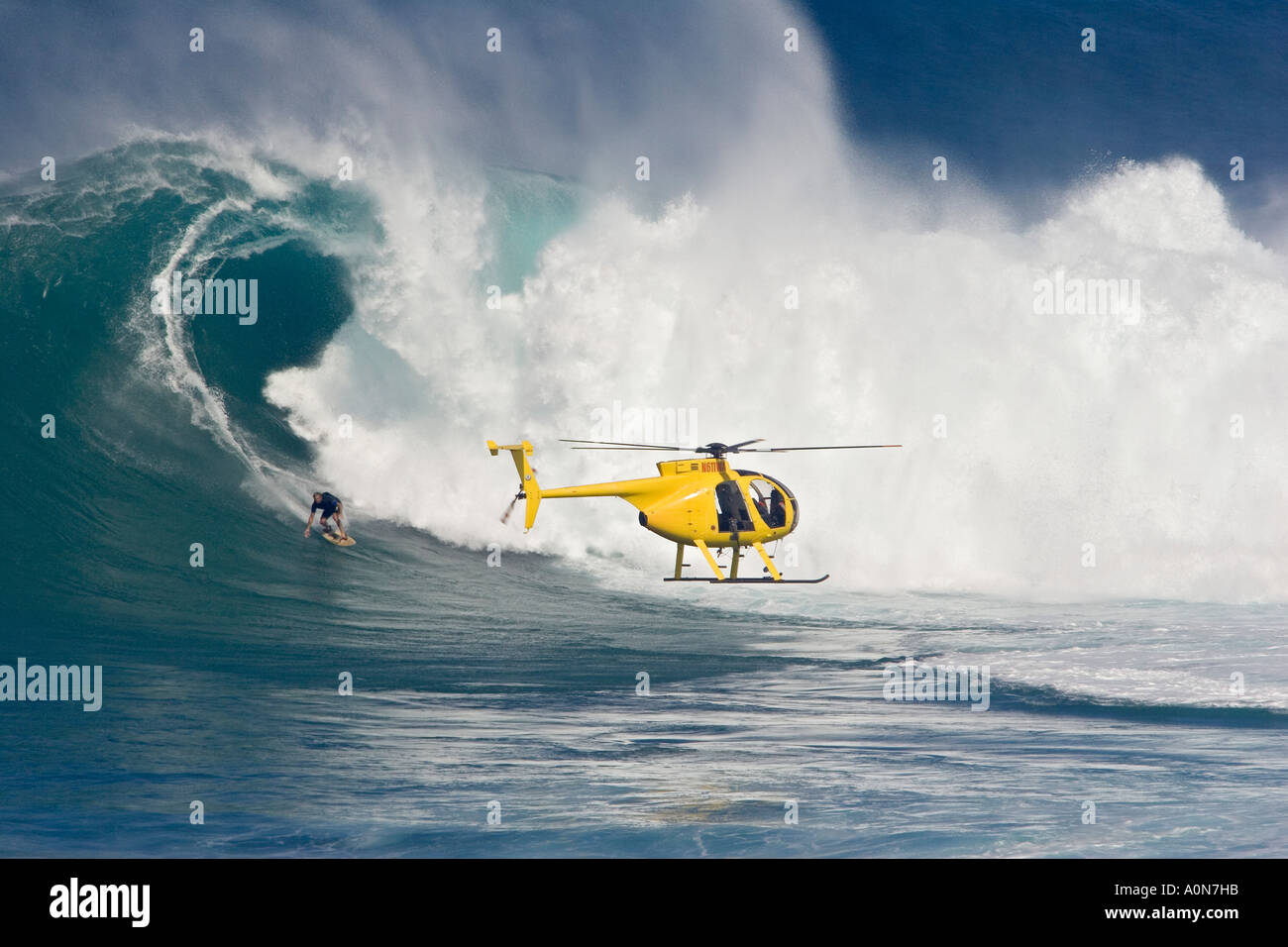 a helicopter filming tow in surfer laird hamilton at peahi jaws off