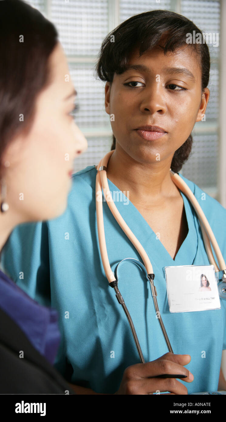 physician or nurse in scrubs listens to female patient or pharma physician or nurse in scrubs listens to female patient or pharma s rep talking to doctor or nurse