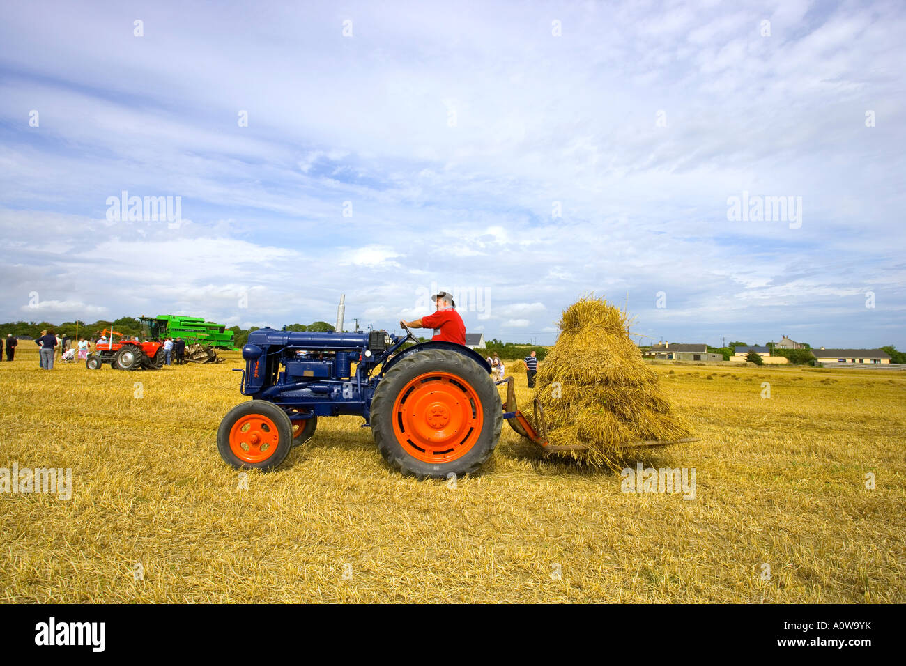 Farmer On Tractor : Farmer on tractor at harvest time in the fields stock