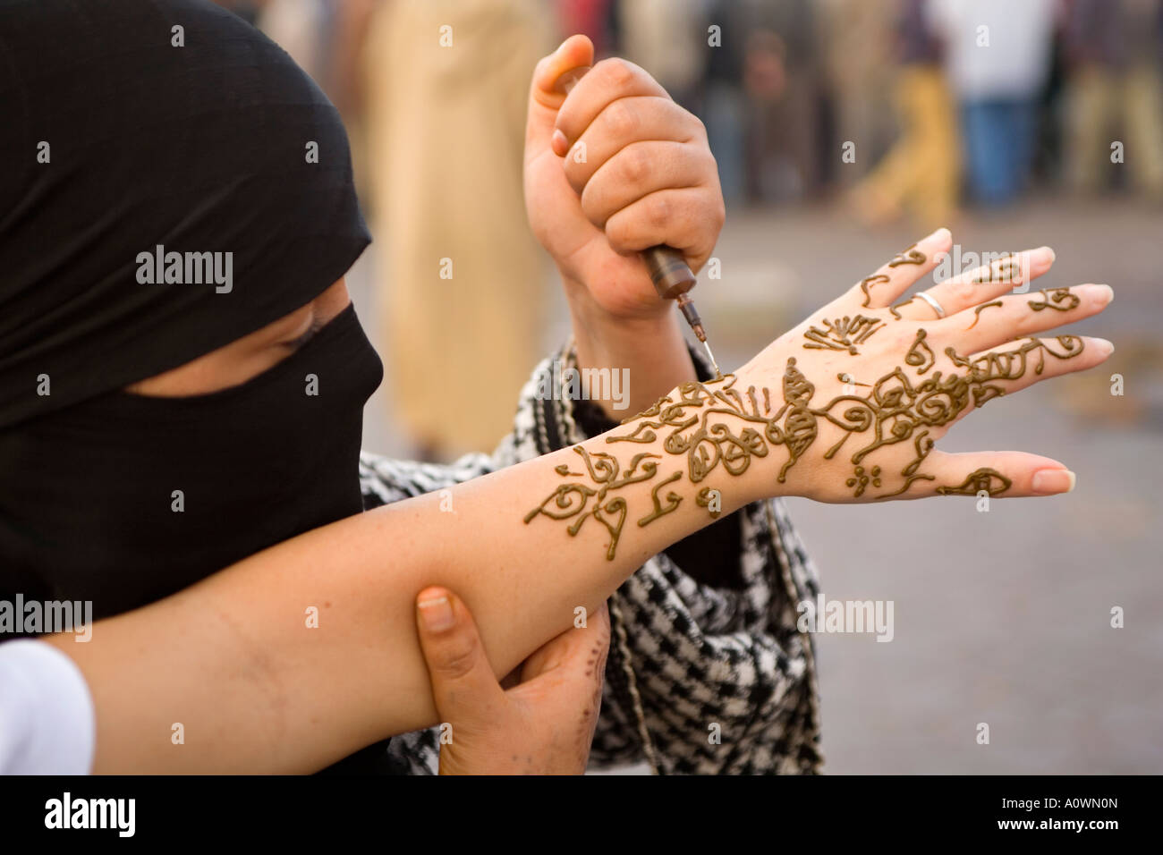 Henna Tattoo Places : Woman applying a henna tattoo on tourists hand in the
