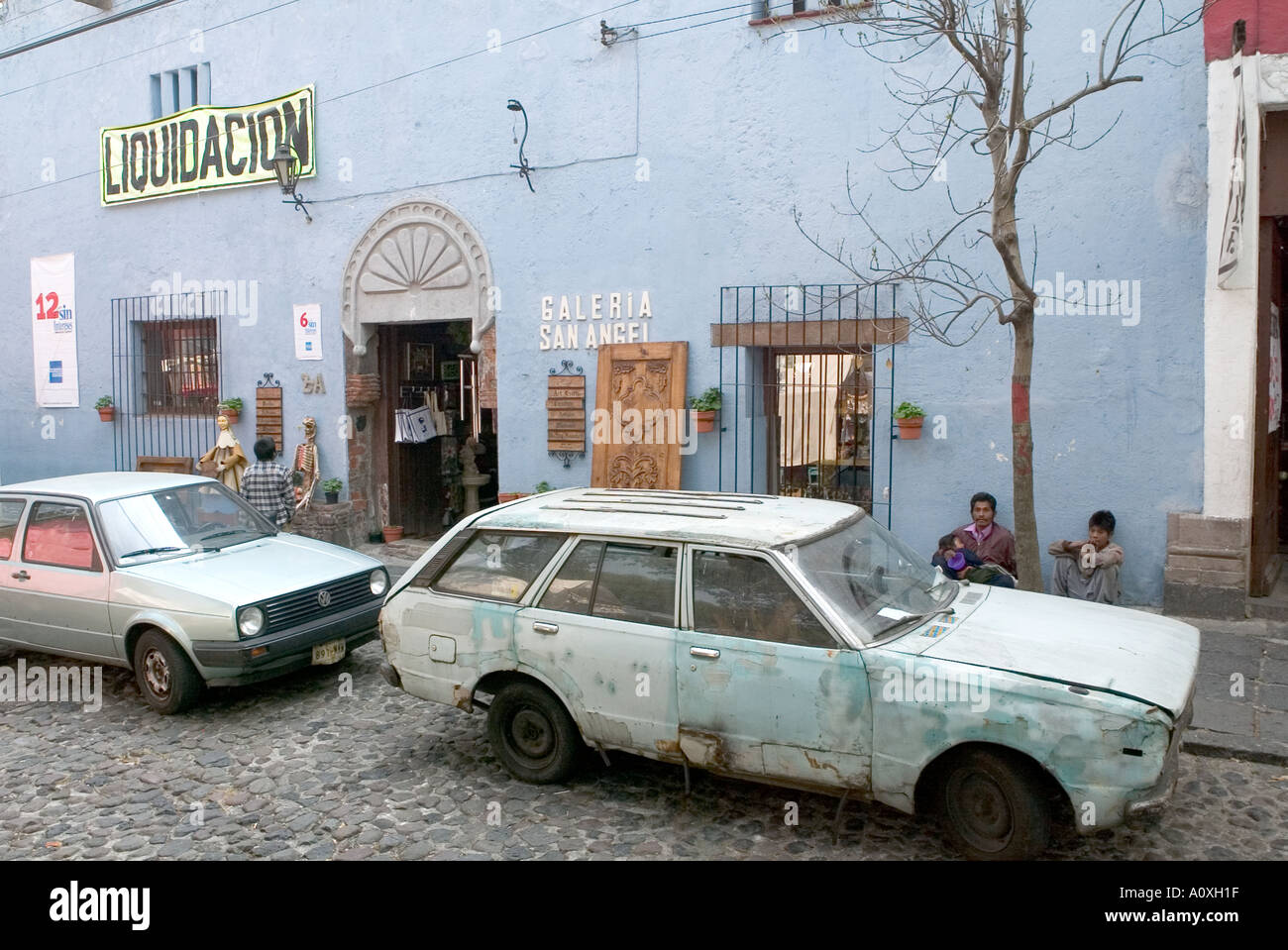 Mexican street showing shop and beggars and broken down old car in ...